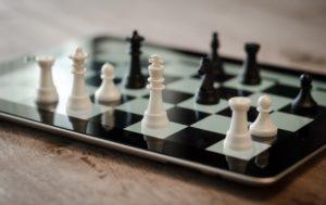 Symbolbild: reale Schachfiguren auf dem Bildschirm des Apple iPads