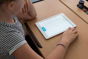 Symbolbild: Speech - Digitalization: Schüler*in mit iPad im Unterricht